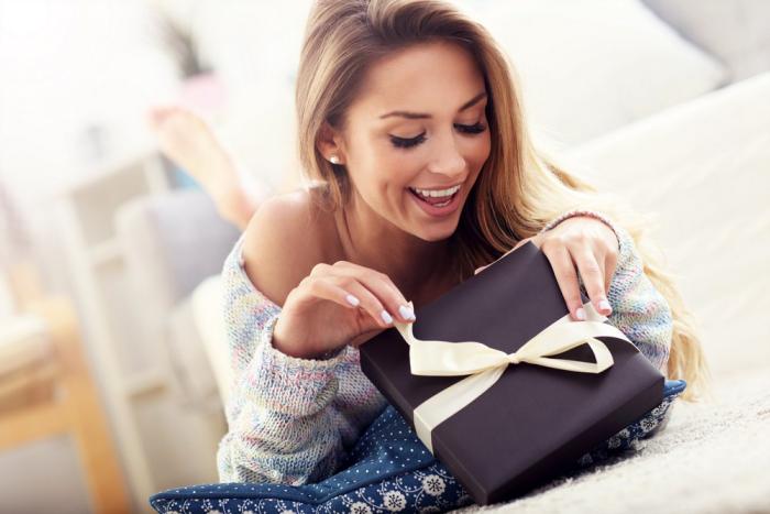 Verliebt sein Sternzeichen eine ausgeprägte romantische Ader junge Frau öffnet Geschenk nette Überraschung
