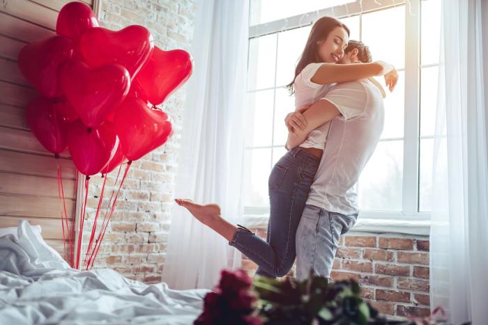 Verliebt sein Sternzeichen zum Valentinstag rote Ballons rote Rosen glücklich sein junges Paar im Schlafzimmer