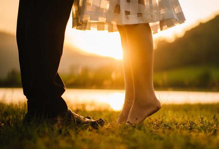 Verliebt sein glücklich sein junges Paar in der Natur bei Sonnenuntergang