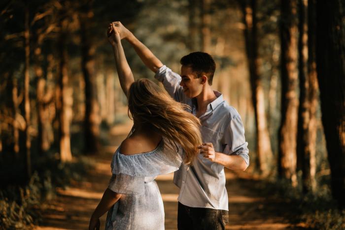 Verliebt sein glückliches junges Paar tanzt im Wald rosarote Brille aufsetzen