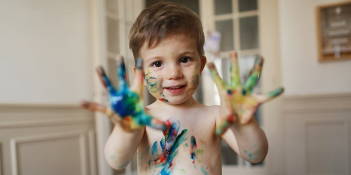 A 2 years old boy doing painting at home