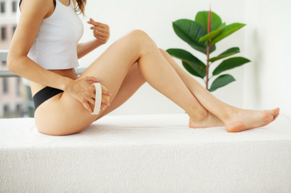 frau bürstet gegen cellulitis mit trockenbürsten