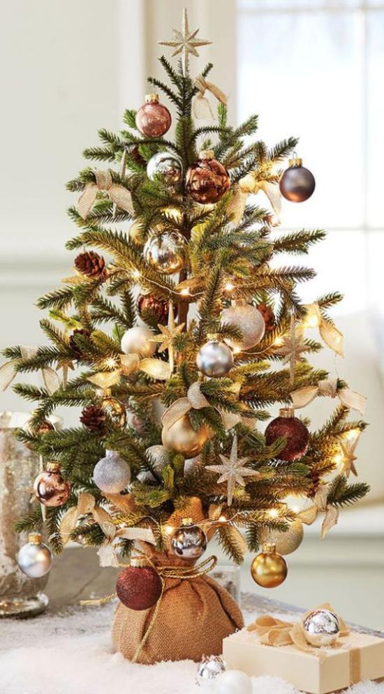 Kleinen Christbaum schmücken zur Schau stellen dunkelrote silberne und goldene Kugeln Sterne im Leinensack