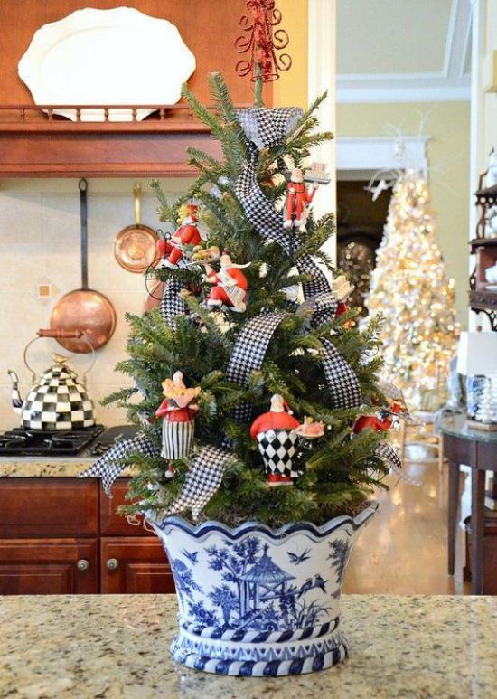 Kleinen Christbaum schmücken zur Schau stellen im schönem blau - weißen Topf Schleife auf der Küchenarbeitsplatte