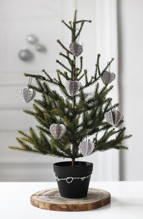 Kleinen Christbaum schmücken zur Schau stellen im schwarzen Topf auf Holzscheibe wenig Schmuck