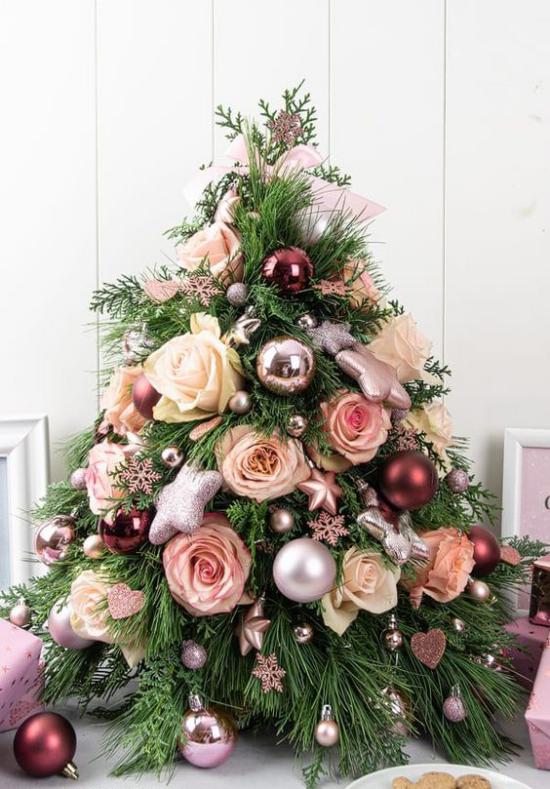 Kleinen Christbaum schmücken zur Schau stellen mit Kugeln und Rosen dekoriert Blickfang