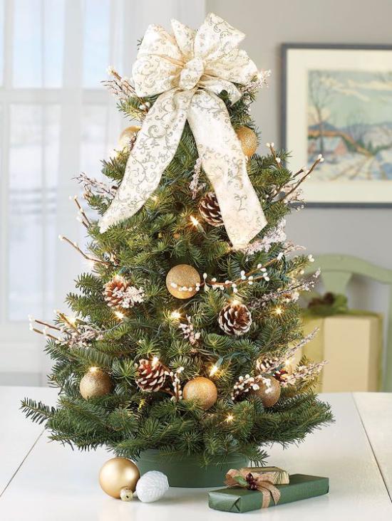 Kleinen Christbaum schmücken zur Schau stellen mit Tannenzapfen große Schleife goldene Kugeln