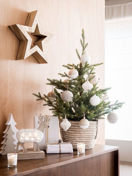 Kleinen Christbaum schmücken zur Schau stellen stilvolle Deko auf der Kommode Stern an der Wand