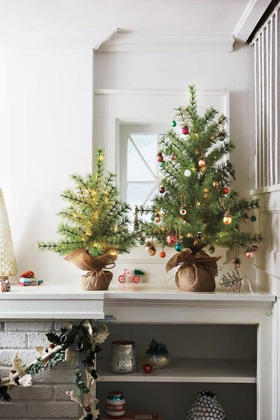 Kleinen Christbaum schmücken zur Schau stellen zwei Mini Weihnachtsbäume neben dem Kamin in der Ecke