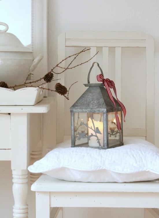 Laternen Weihnachtsdeko drinnen und draußen alte Laterne aus Zink weiße Kerze drinnen brennt auf einem Stuhl neben einem Tisch