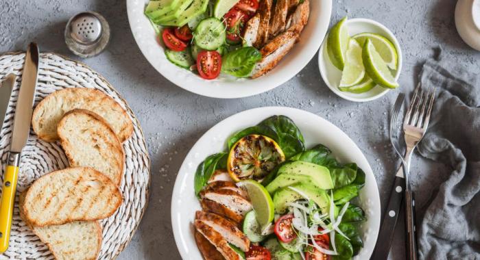 OMAD-Diät eine Mahlzeit pro Tag Fleisch gebraten Beilage grünes Gemüse Tomaten Avocado getoastetes Brot