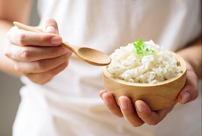 Reisdiät ein einziges Lebensmittel gekochter Reis in einer kleinen Schale aus Holz Blätter Petersilie