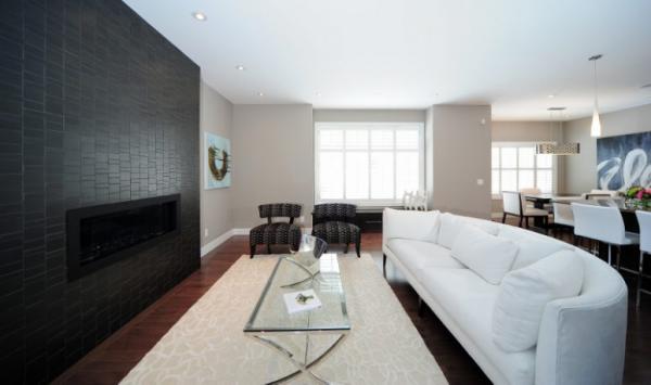 Schwarze Wand Blickfang geräumiges Wohnzimmer weiße Couch Teppich zwei Sessel Kaffeetisch aus Glas