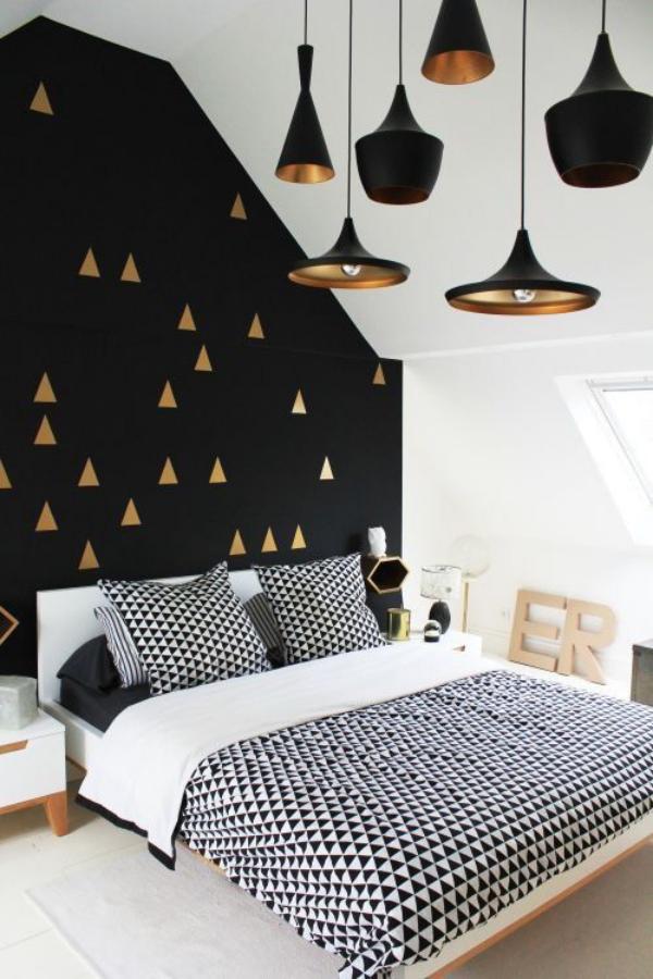 Schwarze Wand Schlafzimmer visuelle Akzente in Gold und Messing Hängelampe gemusterte Bettwäsche lenkt den Blick ab