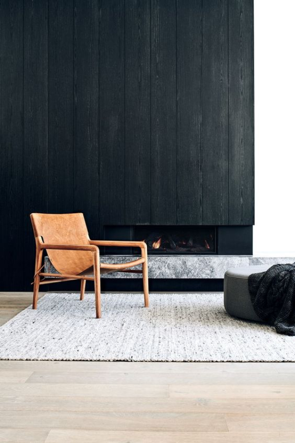 Schwarze Wand Wohnzimmer Kamin ein Stuhl vor dem dunklen Hintergrund grauer Hocker Teppich