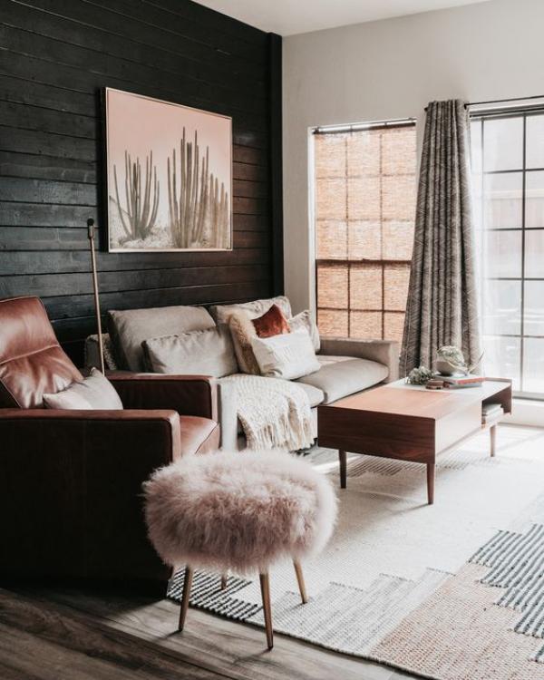 Schwarze Wand gemütliches Wohnzimmer Gemälde an der Wand Sofa Sessel Hocker Kissen in Rosa Beige Grau