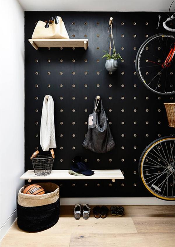 Schwarze Wand im Flur aufgehängte Fahrräder Beutel weißes Handtuch andere Alltagsgegenstände