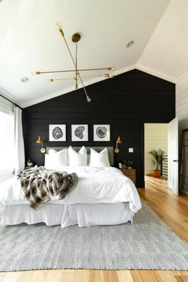 Schwarze Wand im Schlafzimmer asymmetrisch hinter dem Schlafbett drei Bilder Wandlampen schicke Raumgestaltung