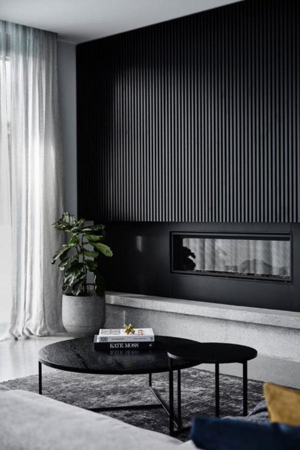 Schwarze Wand im Wohnzimmer als Akzent einzelne Bereiche visuell definieren mit viel Grau kombiniert