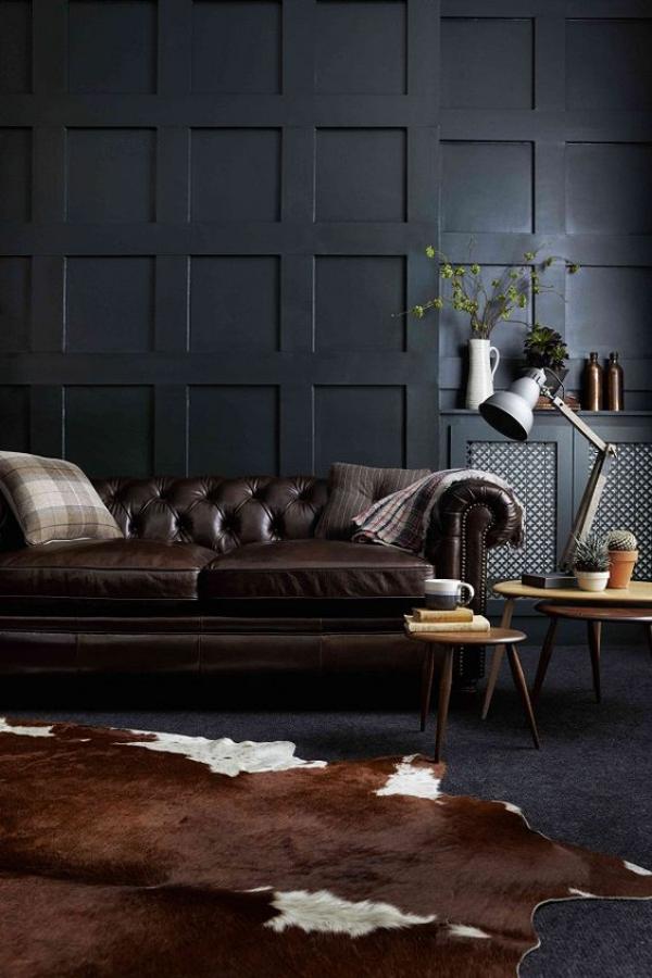 Schwarze Wand im Wohnzimmer schokoladenbraunes Ledersofa Kuhfellteppich Kissen zwei kleine runde Tische aus hellem Holz