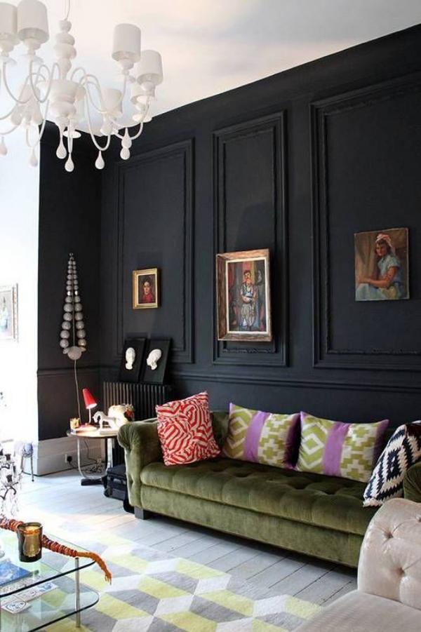 Schwarze Wand im Wohnzimmer viele Deko Artikel Bilder Kristallkronleuchter grüne Ledercouch bunte Kissen