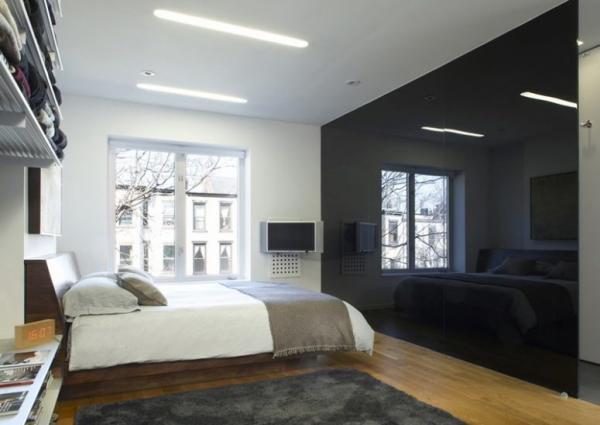 Schwarze Wand in Hochglanz als Akzent ein geräumiges Schlafzimmer Weiß und Grau