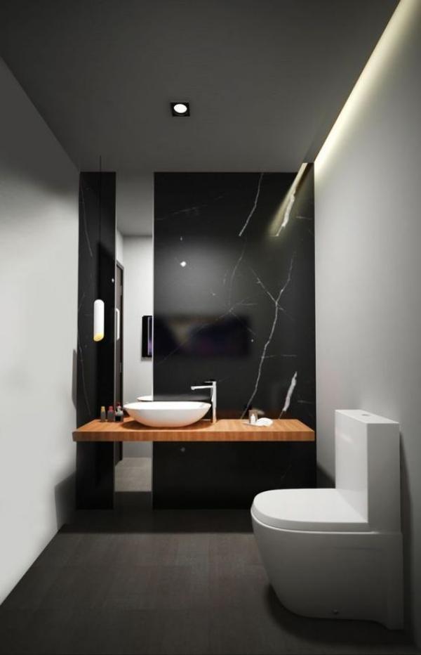 Schwarze Wand modernes Bad WC Akzentwand aus schwarzem Marmor Bodenfliesen in Anthrazit weißes Waschbecken Waschtisch aus Holz