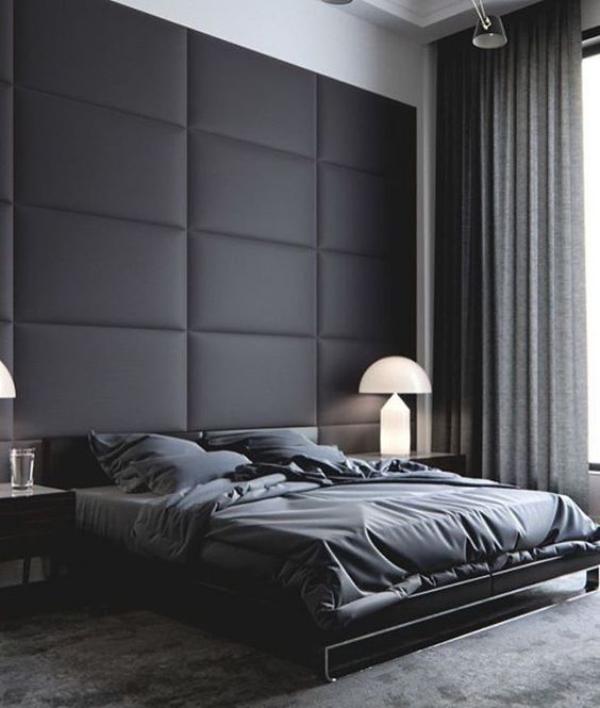 Schwarze Wand stilvoll eingerichtetes Schlafzimmer mit schwarzem Leder gepolsterte Akzentwand hinter dem Schlafbett graue Gardinen Bettwäsche grauer Teppich