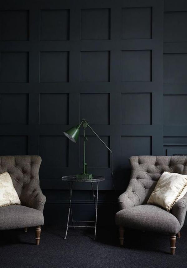 Schwarze Wand zwei Sessel in Beige kleiner runder Tisch dazwischen eine Lampe darauf