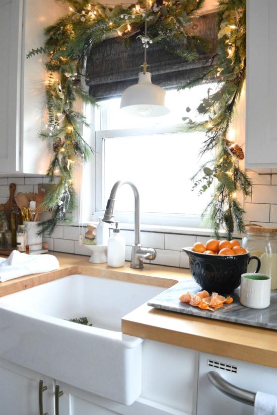Weihnachtliche Fensterdeko Girlande am Küchenfenster Tannengrün glitzernde Kugeln LED Lichter