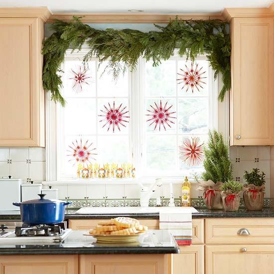 Weihnachtliche Fensterdeko Girlande aus Tannengrün am Küchenfenster hängende Sterne