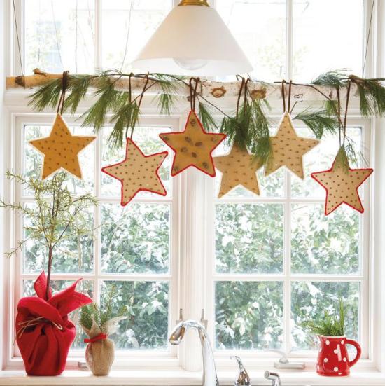 Weihnachtliche Fensterdeko Küchenfenster schmücken Birkenast bunte Sterne aufgehängt Tannengrün dazu