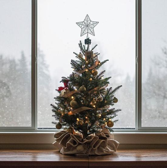 Weihnachtliche Fensterdeko ein kleiner stilvoll geschmückter Christbaum im Topf Leinensack Stern goldglitzernde Kugeln