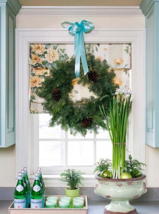 Weihnachtliche Fensterdeko großer Kranz aus Tannengrün Zapfen blaue Schleife am Küchenfenster