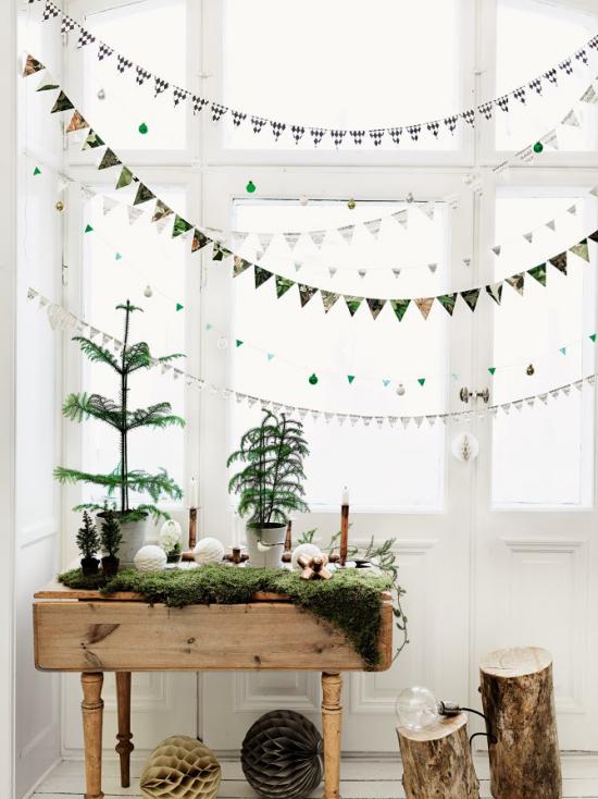 Weihnachtliche Fensterdeko hängende Girlanden Sterne Dreiecke vorne rustikal geschmückter Tisch