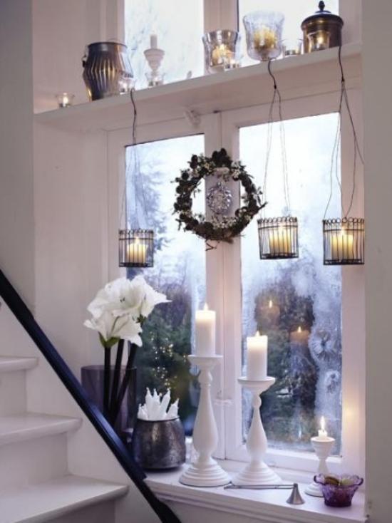 Weihnachtliche Fensterdeko schöner Fensterschmuck von draußen zu sehen Vase mit weißen Blumen drei weiße Kerzen hängende Teelichter kleiner Kranz