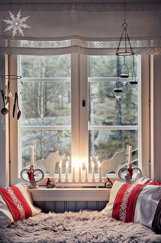 Weihnachtliche Fensterdeko weiße Holzfiguren Kerzen auf der Fensterbank Teelichter hängen