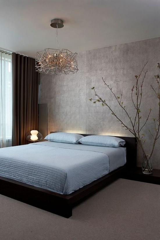 Zen Schlafzimmer schönes Raumdesign, hellblaues Bettlaken dezentes Licht hinter dem Bett Nachttischlampe blühende Zweige