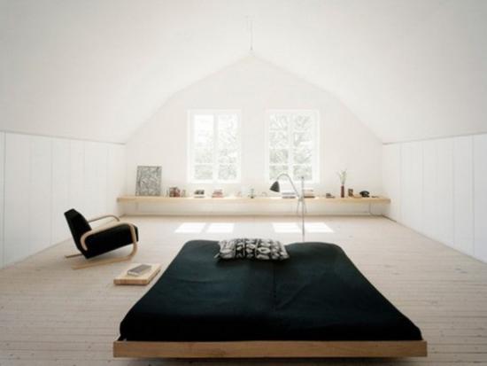Zen Schlafzimmer weite freie Raumfläche großes Fenster bequemes Schlafbett schwarzer Sessel
