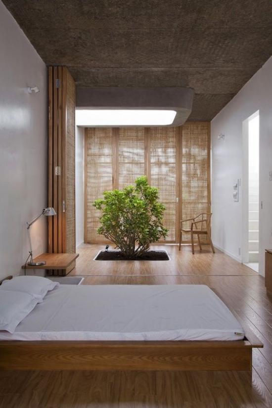 Zen Schlafzimmer weites Schlafbett helle Bettwäsche viel Holz großes abgedunkeltes Fenster ein kleiner Baum grüne Note