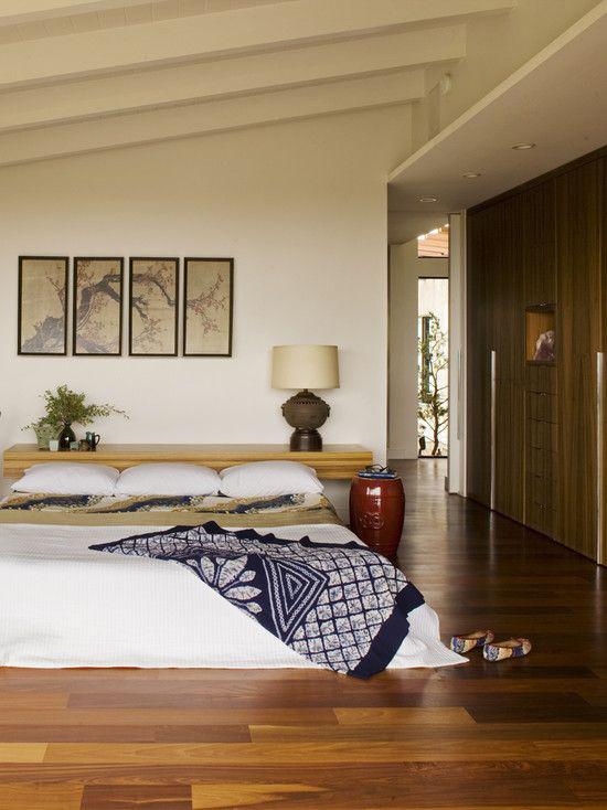 Zen Schlafzimmer weites komfortables Schlafbett Kissen visuelle Akzente gemusterte Decke in Dunkelblau und Grau hohe Vase in Karminrot neben dem Bett