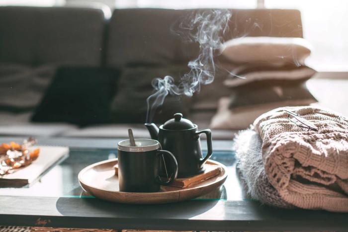 gesund und glücklich im Winter bleiben aromatischer Tee duftet auf dem Kaffeetisch kuschelweiche Decken daneben