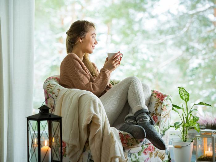 gesund und glücklich im Winter bleiben gemütlich machen zu Hause Frau im Sessel Tee trinken Relax eine grüne Pflanze daneben