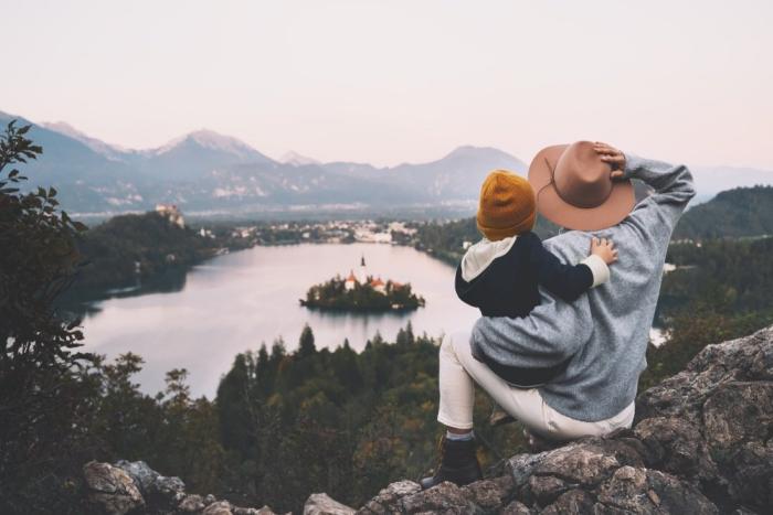gesund und glücklich im Winter bleiben junge Frau Kleinkind Kurzreise romantischer Panoramablick über einen See kleine Insel altes Schloss