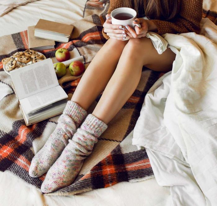 gesund und glücklich im Winter bleiben junge Frau im Bett kleine Süßigkeiten Äpfel heißer Tee angenehme gemütliche Atmosphäre