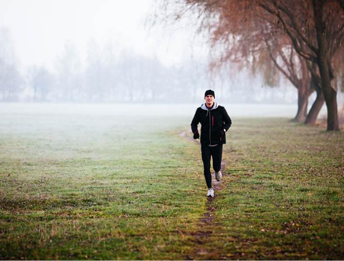gesund und glücklich im Winter bleiben junger Mann joggen bei schlechtem Wetter fit sein