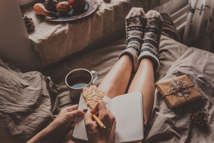 gesund und glücklich im Winter bleiben junges Mädchen im Schlafzimmer Relax pur weiche Bettwäsche Aromen Tee