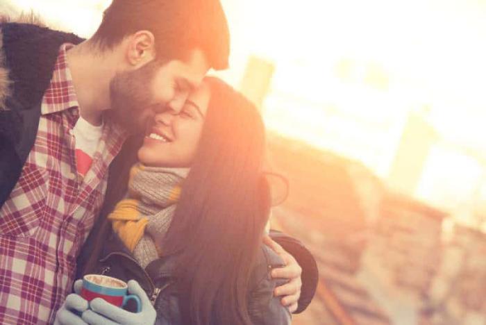 gesund und glücklich im Winter bleiben junges Paar kuschelt lacht trotz der Kälte