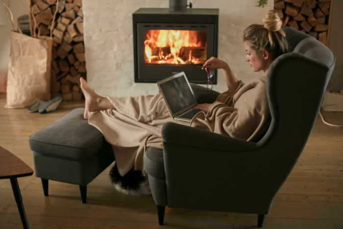 gesund und glücklich im Winter junge Frau im Sessel vor dem brennenden Kamin ein Buch in der Hand Brennholz warme gemütliche Raumatmosphäre