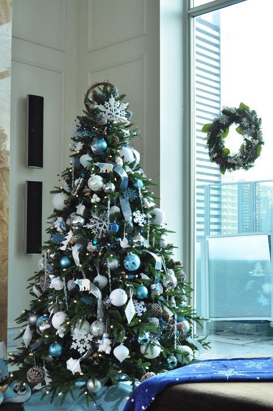 Blau und Silber Weihnachten und Silvester feiern Christbaum geschmückt neben dem Fenster Kranz an der Glasscheibe